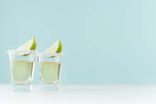 Golden Mexican Tequila Shot Drinks With Salty Rim, Piece Lime In Elegant Glass On Pastel Green Wall, White Wood Table, Copy Space.
