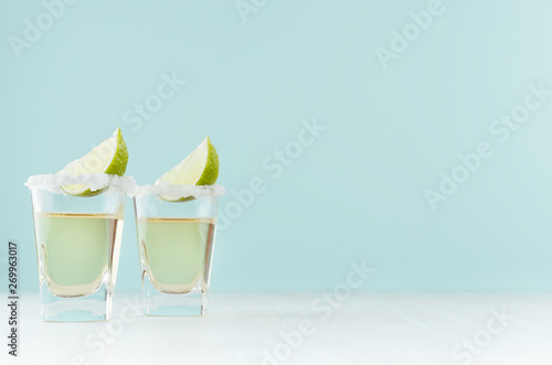 Fotografie, Obraz  Golden mexican tequila shot drinks with salty rim, piece lime in elegant glass on pastel green wall, white wood table, copy space