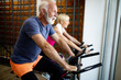 canvas print picture - Mature fit people biking in the gym, exercising legs doing cardio workout cycling bikes