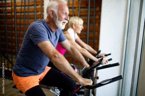 fototapeta na drzwi i meble Mature fit people biking in the gym, exercising legs doing cardio workout cycling bikes