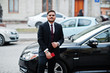 Stylish indian businessman in formal wear with mobile phone standing against black business car on street of city.