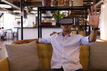 Businessman Using Virtual Reality Headset In Office