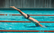 Young Male Swimmer Jumping Int...