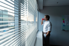Young Male Executive With Hand In Pocket Drinking Coffee Near Window In A Modern Office