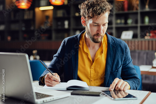 Young serious Caucasian busienssman using tablet and writing notes in agenda while sitting in cafe.