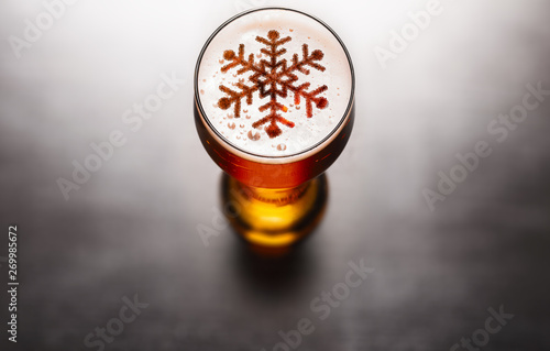 Deurstickers Alcohol Christmas or New Year beer concept. Snow symbol on beer glass foam on black table, view from above