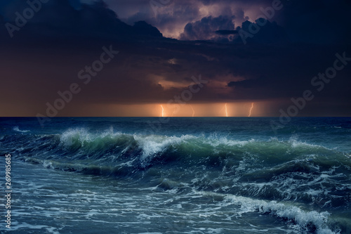 Huge lightnings in dark stormy sky above waving sea Fototapeta