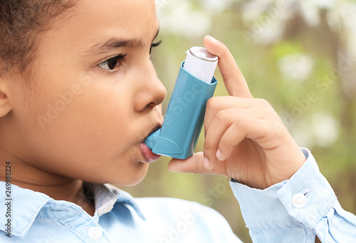 Photo African-American girl with inhaler having asthma attack outdoors on spring day