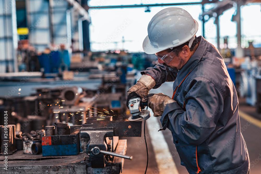 Fototapety, obrazy: Skilled industrial worker grinding metal part.