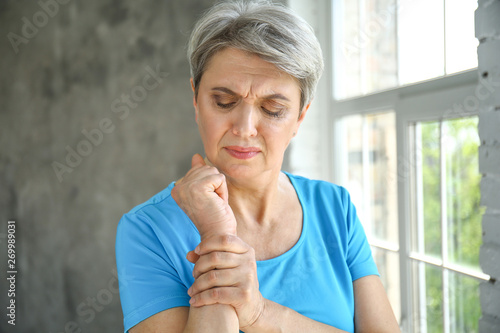 Mature woman suffering from pain in wrist at home Canvas Print