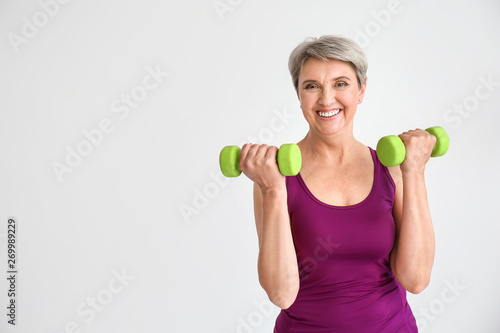 Leinwand Poster Sporty mature woman with dumbbells on light background