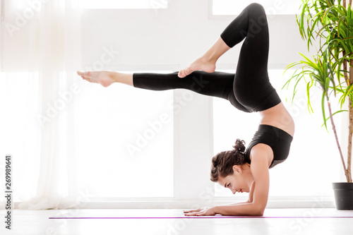 Fotografia  Young healthy fitness beautiful woman female doing vrischikasana yoga posture and yoga workout on yoga mat at yoga studio in morning