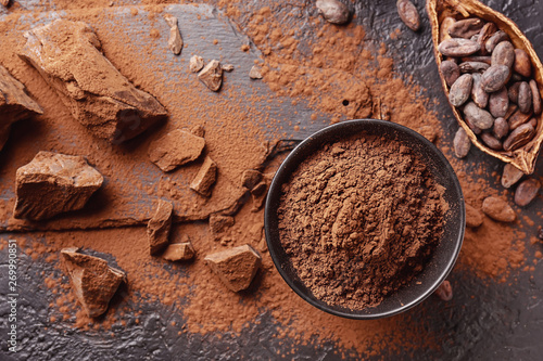 Composition with cocoa powder, beans and chocolate on table