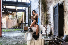 Portrait Of Natural Model In Abandoned Building Hanging On A Washing Machine And Smoking A Cigar