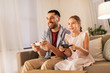 canvas print picture - family, gaming and entertainment concept - happy father and little daughter with gamepads playing video game at home