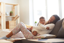 Smiling Careful Loving Young African Mother With Wavy Hair Sitting On Comfortable Sofa And Hugging Baby While They Relaxing Together