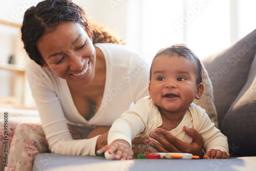 Fototapeta Positive loving young black mother spending beautiful time with her baby on mate