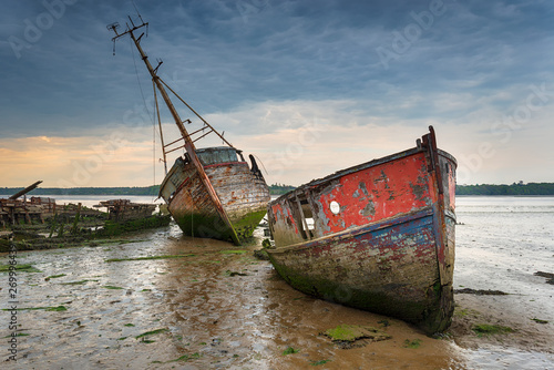 Old boat wrecks under a stormy sky Wallpaper Mural