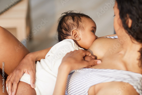 Fototapeta Close-up of young black mother attaching baby at breast while giving nipple to son during breastfeeding obraz