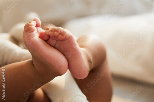 Fotografia Close-up of unrecognizable cute baby shaking feet while lying in bed, innocence