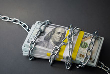 Bundle Of Dollars Tied Up With A Chain, The Concept Of Credit Slavery, Debt, Seized Assets. Dark Background, Closeup