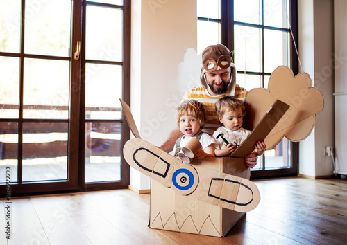 A father and toddler chidlren playing with carton plane indoors at home Fototapete