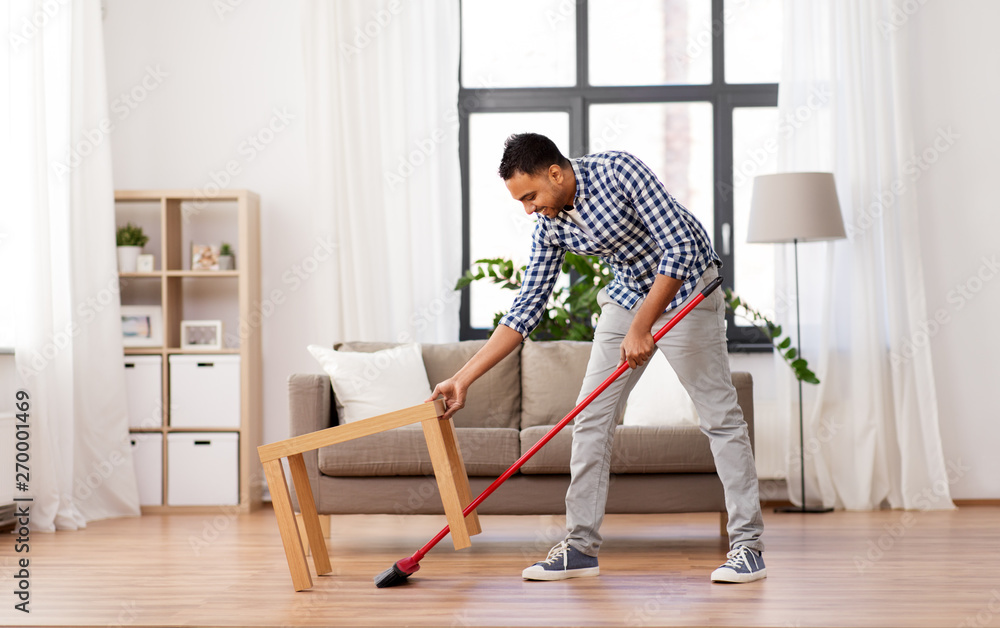 Fototapeta cleaning, housework and housekeeping concept - indian man with broom sweeping floor at home