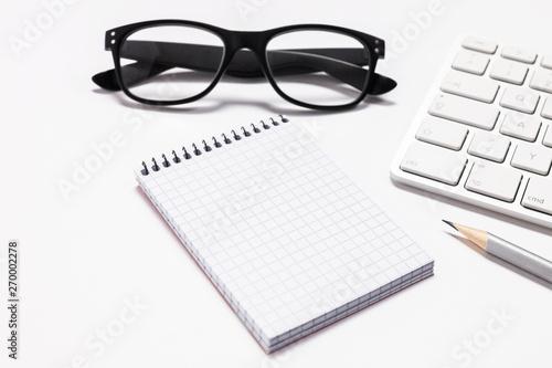 Fotografie, Obraz  Auf dem Tisch liegt ein karierter Notizblock, dazu eine Tastatur und eine Brille