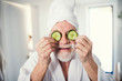 canvas print picture - Senior man with cucumber on front of his eyes in bathroom indoors at home.