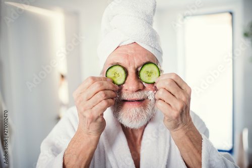 Recess Fitting Equestrian Senior man with cucumber on front of his eyes in bathroom indoors at home.