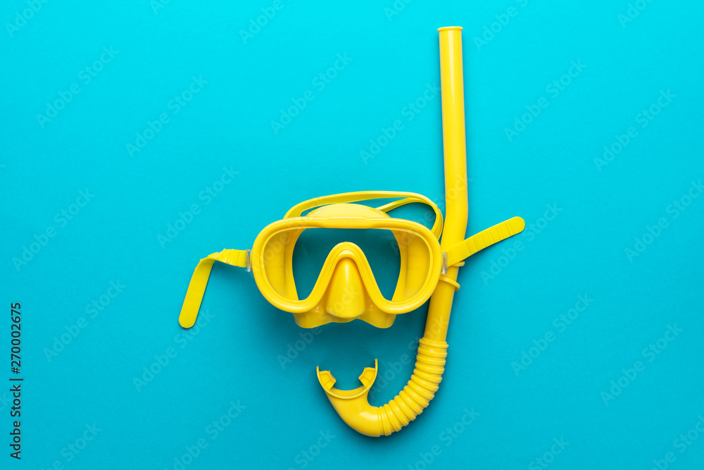 Fototapeta flat lay shot of yellow diving mask with snorkel over turquoise blue background. minimalist photo of dive mask and snorkel with central composition