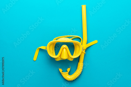 Fototapeta flat lay shot of yellow diving mask with snorkel over turquoise blue background. minimalist photo of dive mask and snorkel with central composition obraz