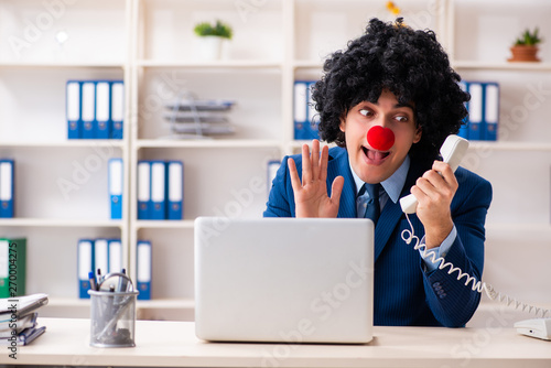 Young clown businessman working in the office Canvas Print