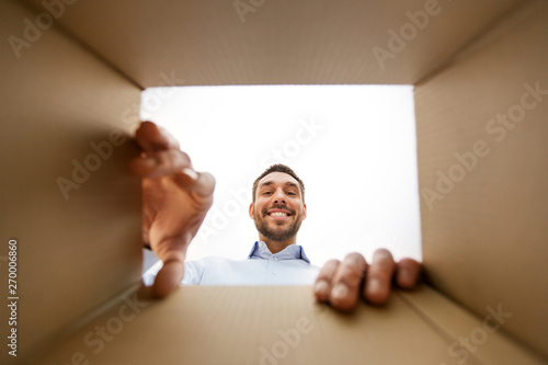 mail delivery and surprise concept - smiling man taking something out of parcel Tablou Canvas