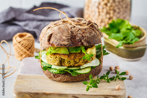 Photo Vegan sandwich with chickpea patty, avocado, cucumber and greens in rye bread