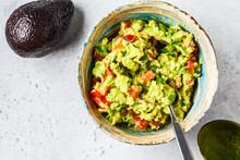 Fresh Avocado Tomato Guacamole In A Bowl. Healthy Plant Based Food Concept.