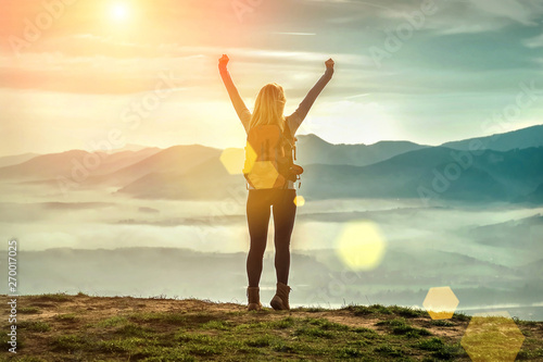 Obraz Happy woman tourist stay with open hands up on the green grass o - fototapety do salonu