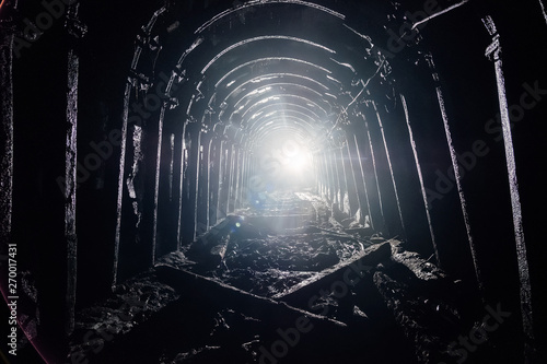 Tablou Canvas Dark abandoned coal mine with rusty lining in backlight