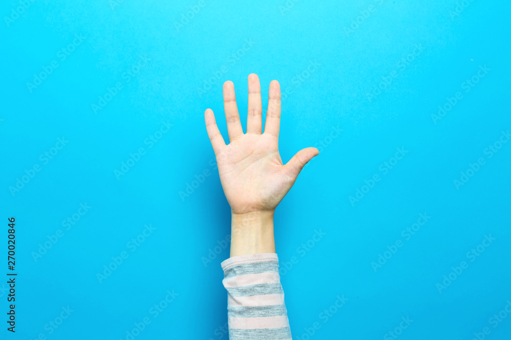 Fototapeta Person raising their hand up on a blue background