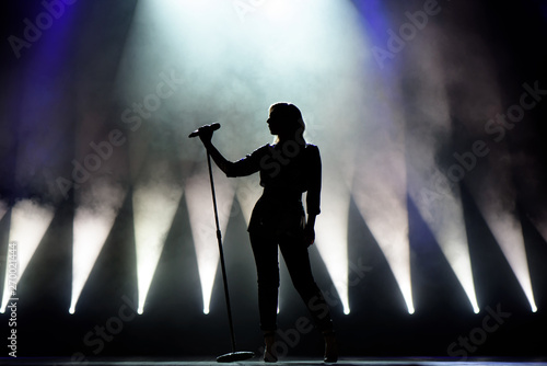 Photo Vocalist singing to microphone. Singer in silhouette