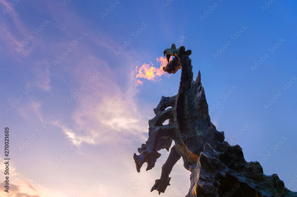 Fototapety, obrazy: Symbol of Cracow - legendary polish wawel dragon monument with fire coming out from its mouth against blue sky at sunset.