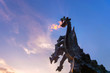 Leinwanddruck Bild - Symbol of Cracow - legendary polish wawel dragon monument with fire coming out from its mouth against blue sky at sunset.