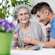 canvas print picture - Seniorin spielt mit Pflegepersonal ein Brettspiel