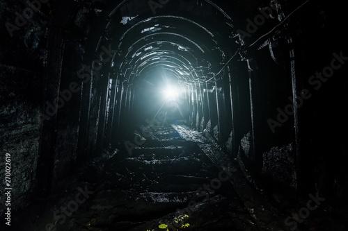 Fotografia Dark abandoned coal mine with rusty lining in backlight