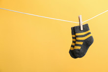 Small Socks Hanging On Washing Line Against Color Background, Space For Text. Baby Accessories
