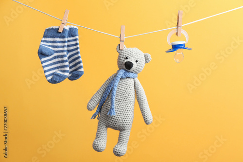 Fotomural  Small socks, pacifier and toy bear hanging on washing line against color background