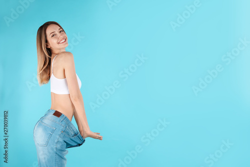 Obraz Slim woman in oversized jeans on color background, space for text. Perfect body - fototapety do salonu