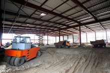 At The Construction Site. View Of A Hangar Building, An Excavator And Dump Trucks Loaded
