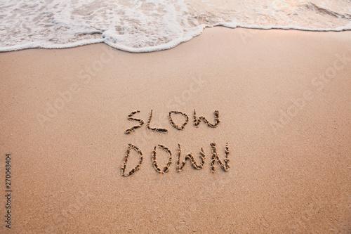 Fotografia slow down, mindfulness concept written on sand