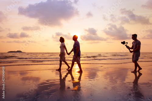 Vászonkép filmmaker filming video of couple with camera stabilizer on the beach at sunset,